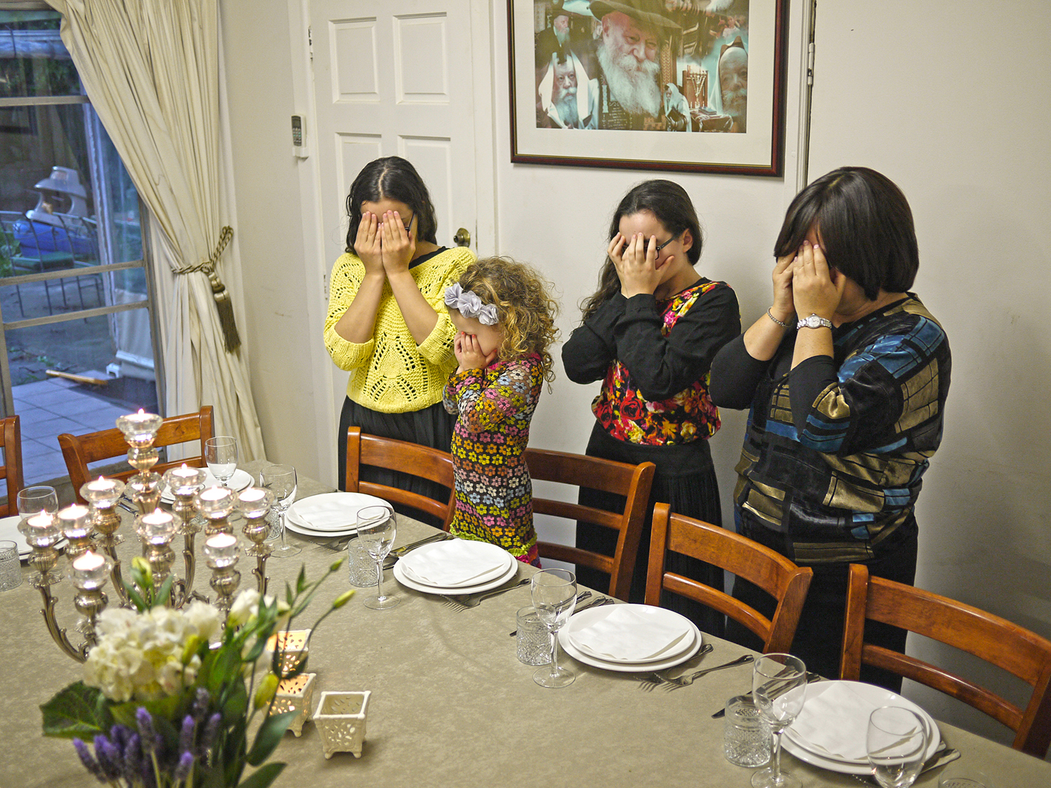 Three girls and a woman stand in front of settings at a dining table with their hands covering their eyes.