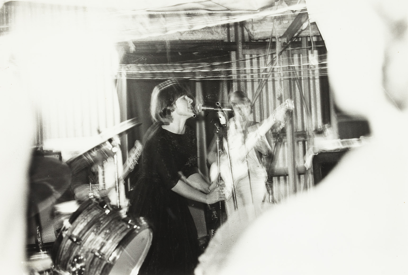 A black and white photo of a singer in a band, with a shaky effect.