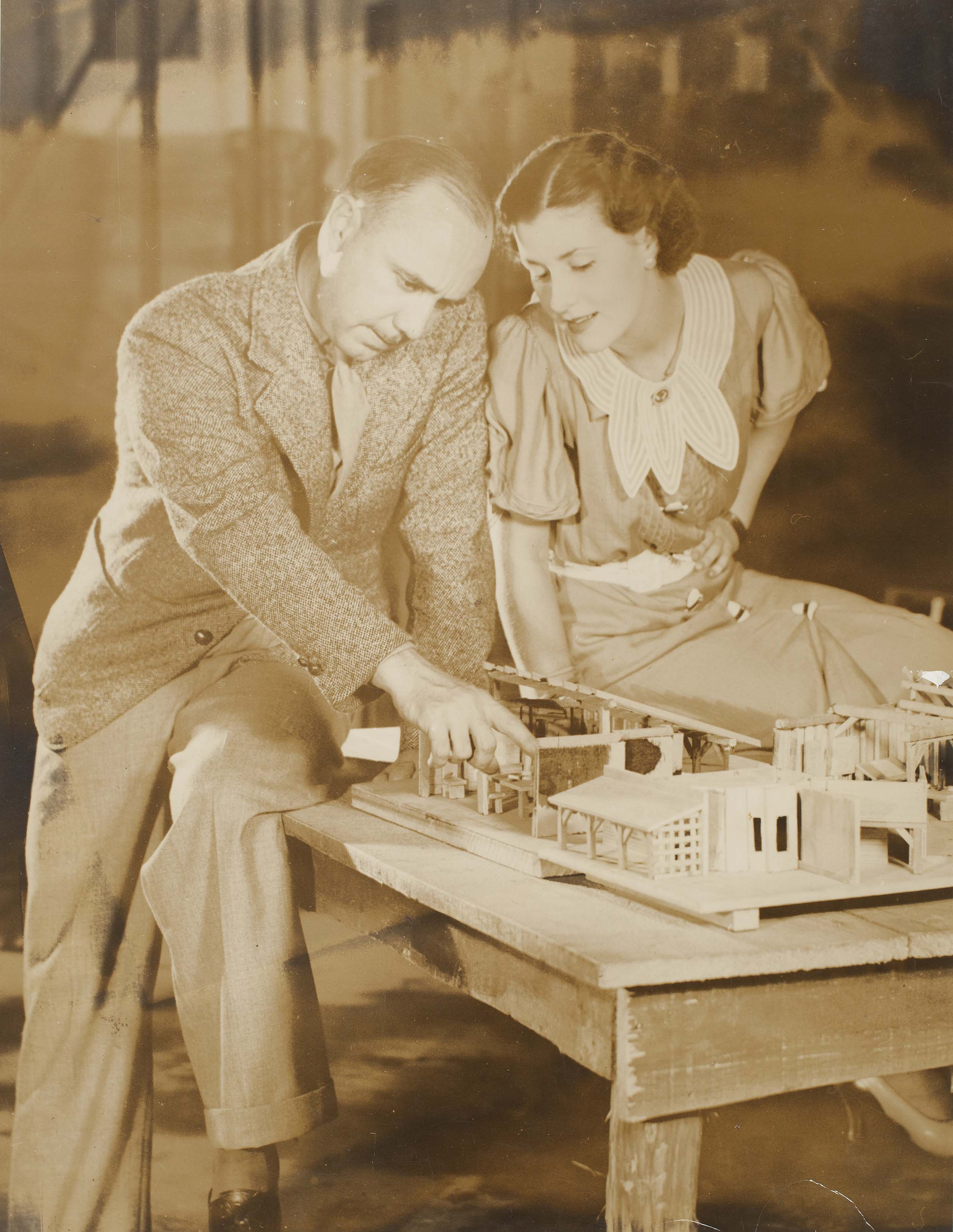 Man and woman looking at miniature house on a table