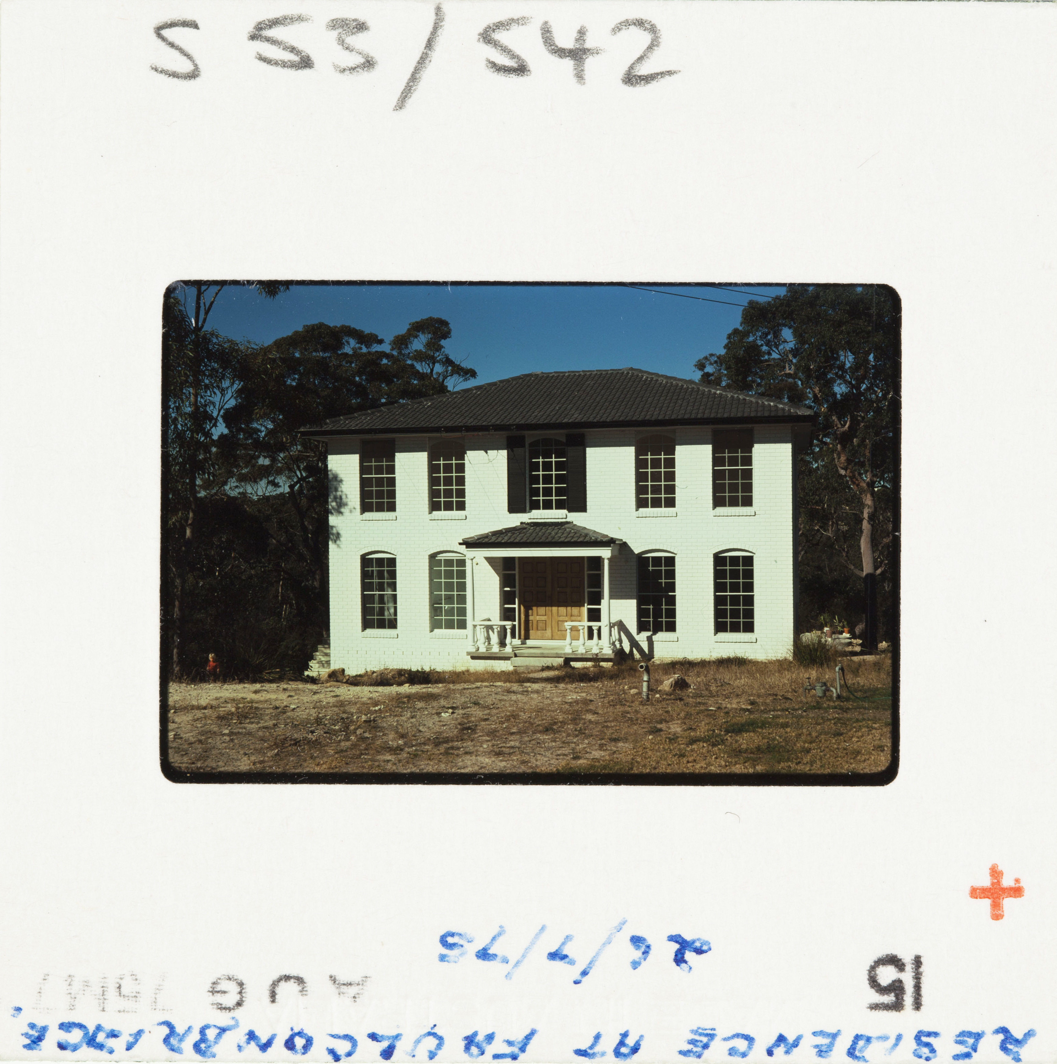 A 70s Kodak colour slide; a white brick house newly built with dry, grassless front yard.