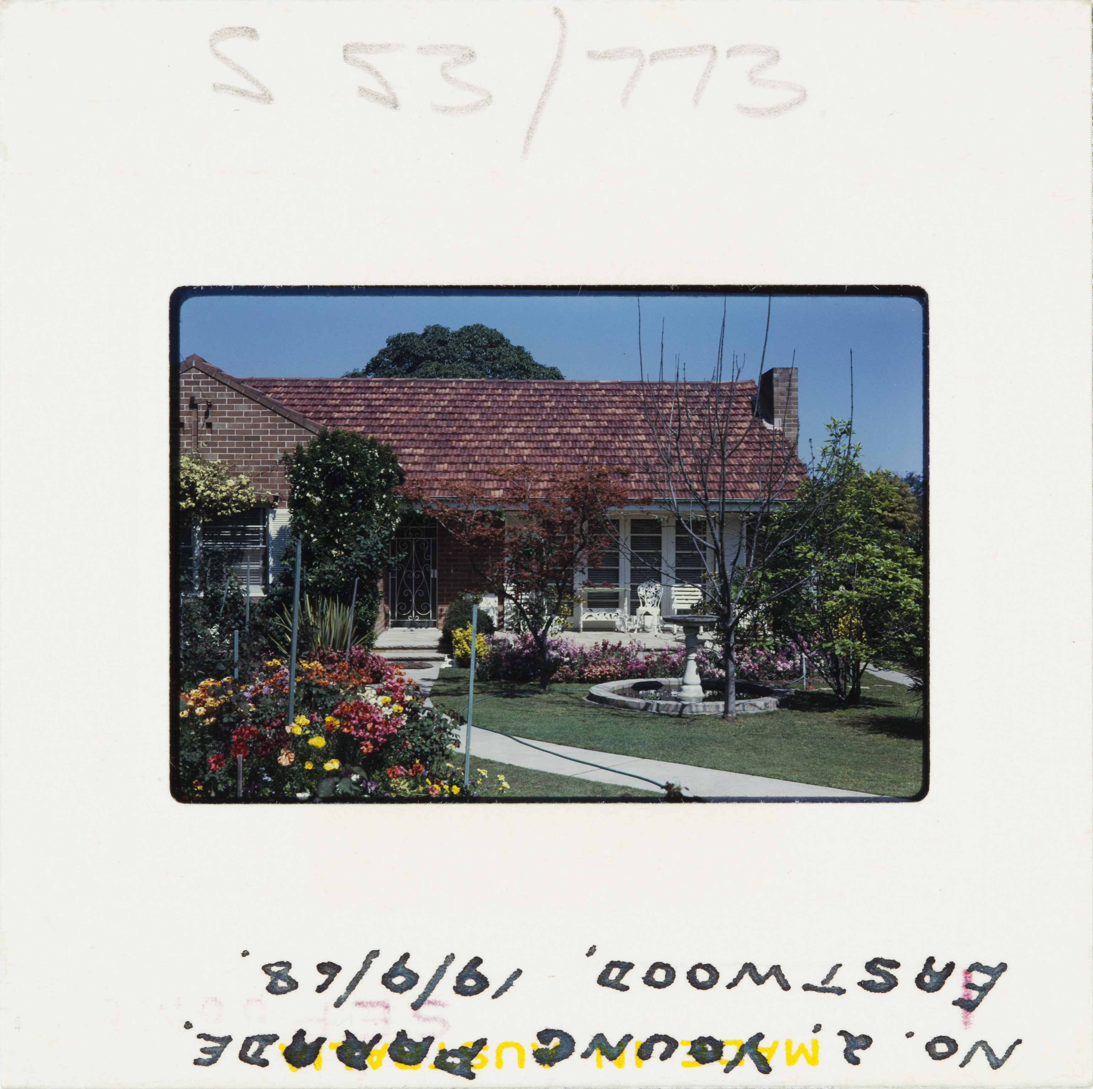 A 60s Kodak colour slide of a suburban brick home with colourful front garden in full flower.