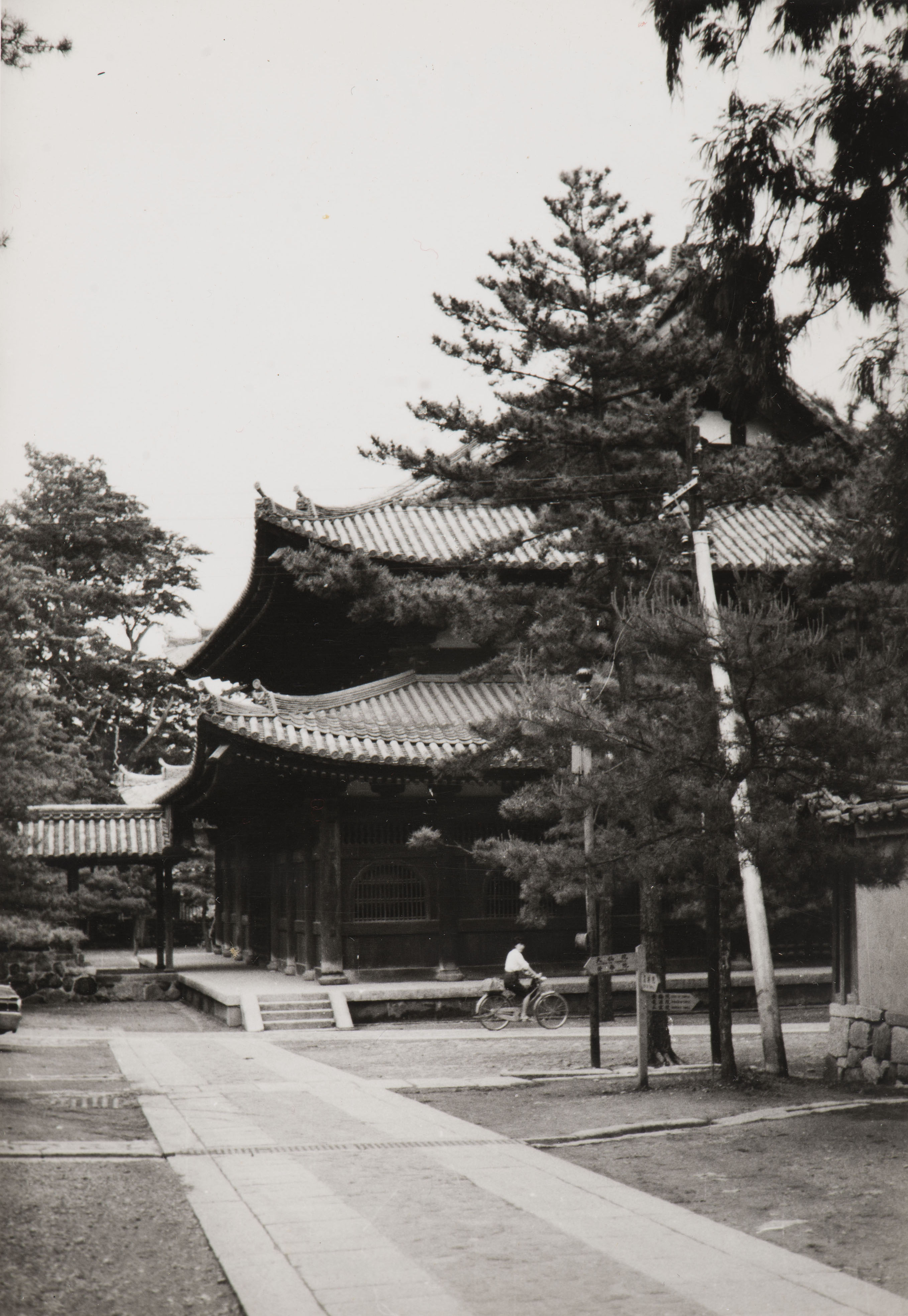 A black and white photograph of a walkway leading to a Japanese temple.