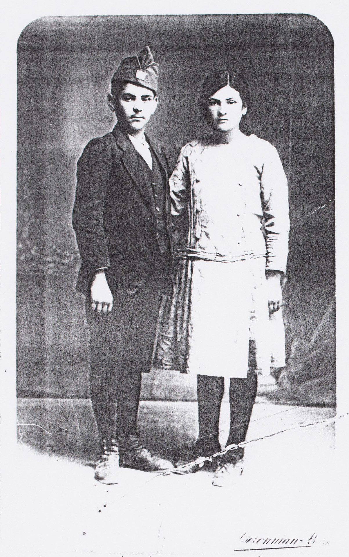 A young teenage boy and girl stand together.
