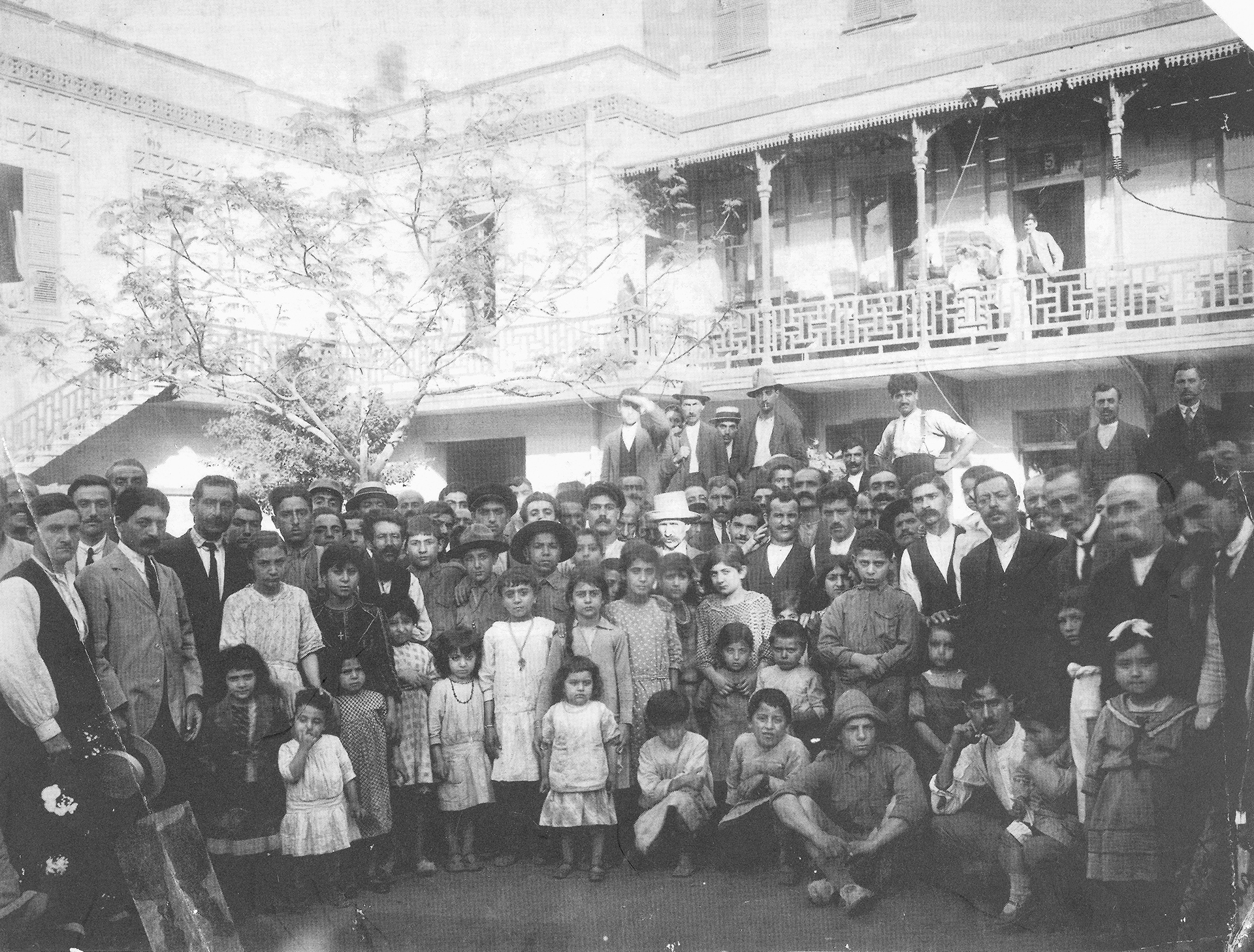 A group of 60 to 70 people in front of a building, with mostly children in the foreground.
