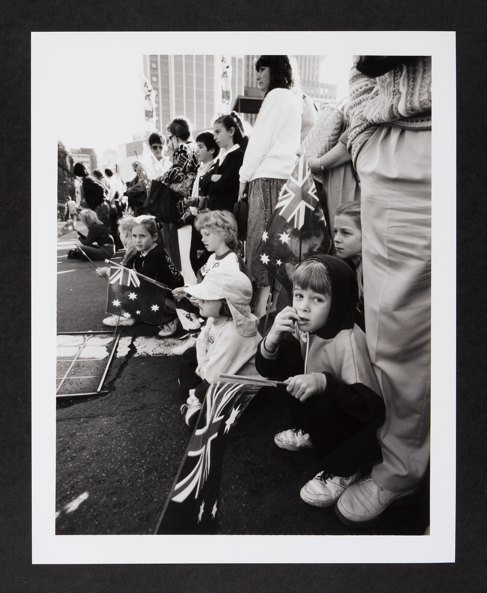 Bystanders, including children, at a parade, holding Australian flags.
