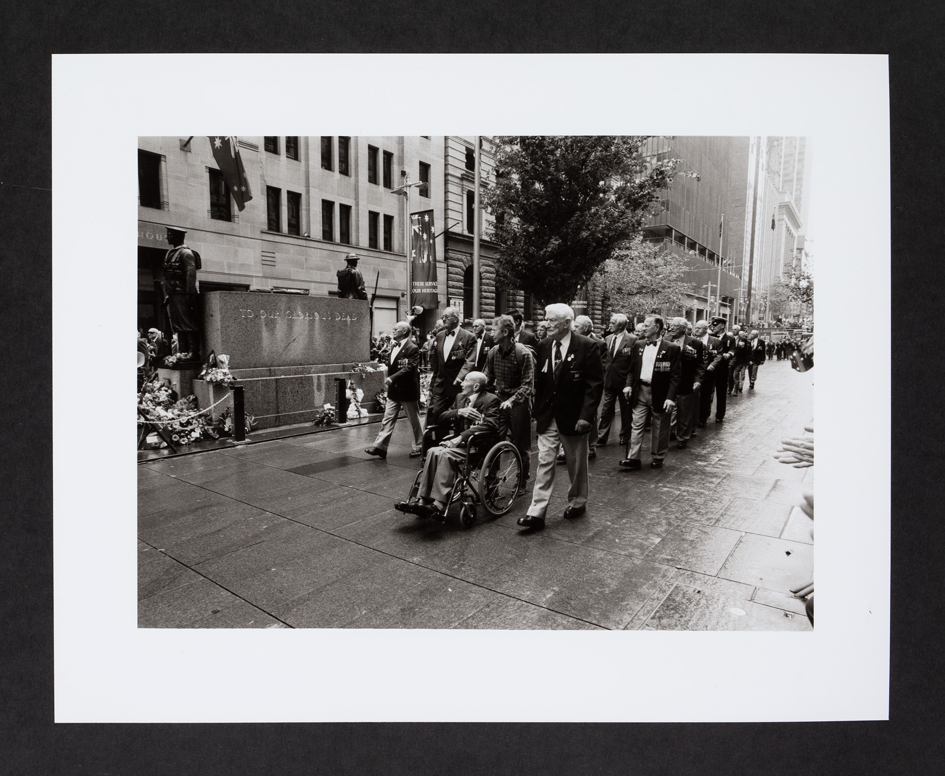 A marching contingent of veterans, one in a wheelchair, past a war memorial.