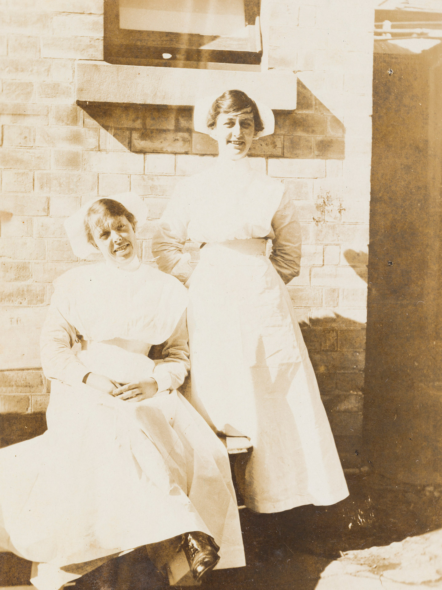 A sepia photograph depicting two women in nurse uniform, smiling.