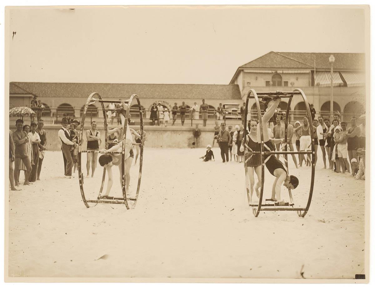 Women standing and turning in giant wheels along Bondi Beach