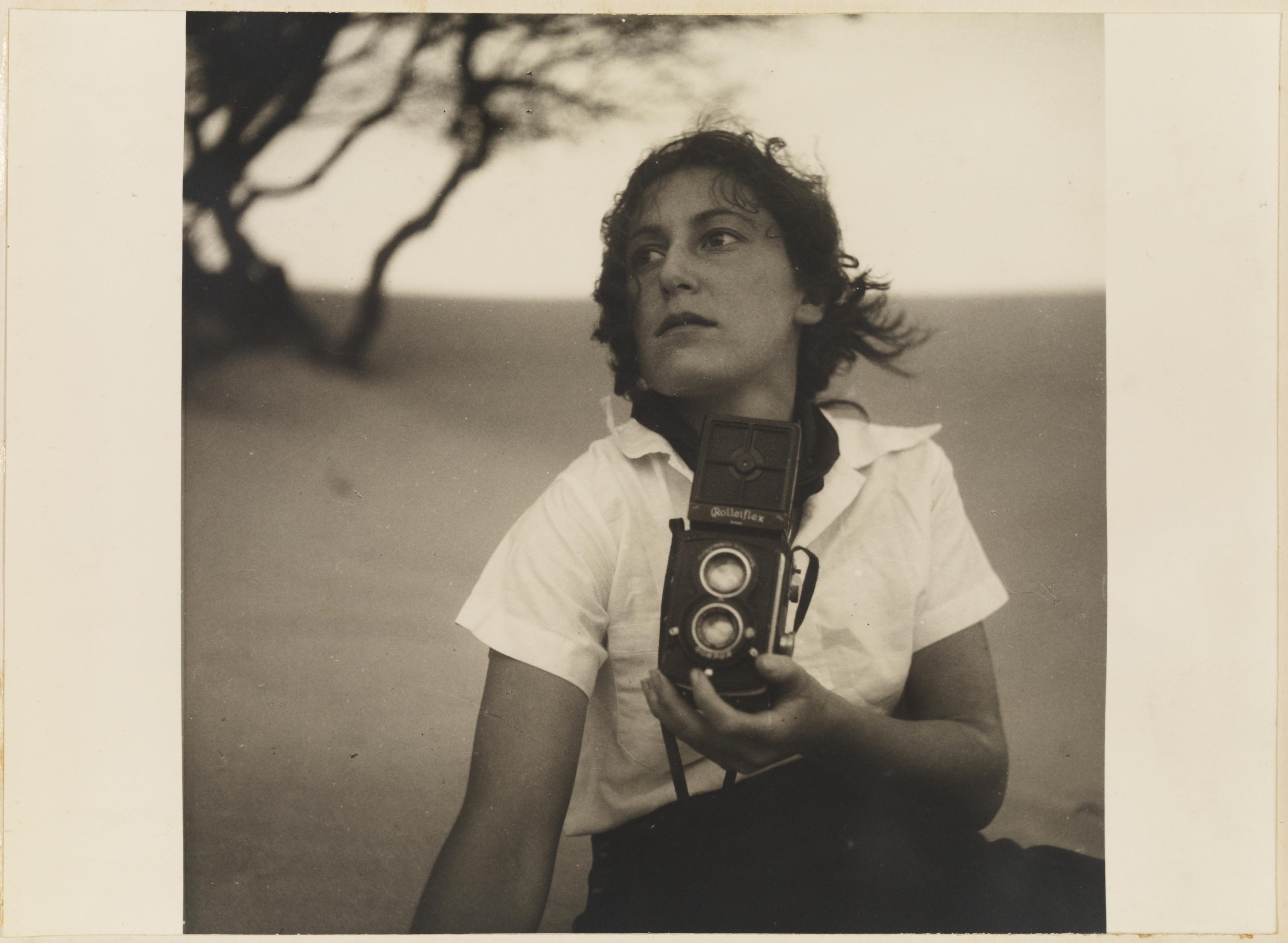 17. Olive Cotton, holding camera