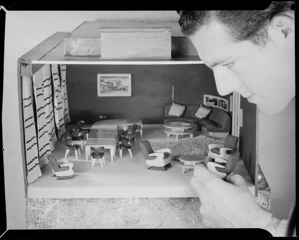 Man playing with dollhouse