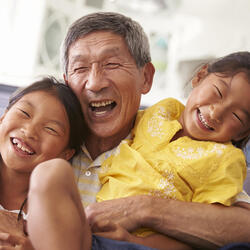 Grandfather hugging and laughing with two young granddaughters