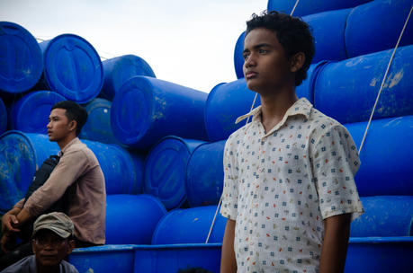 Two teenage boys standing in front of a stack of blue barrels