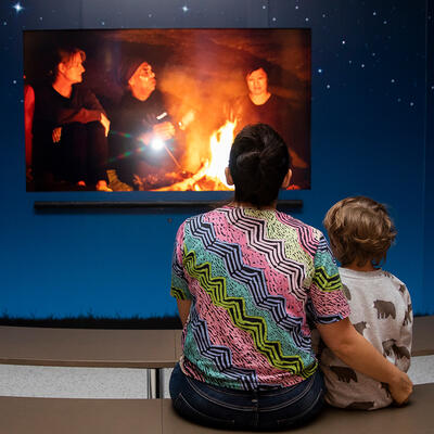 A woman and a child watch a video clip.