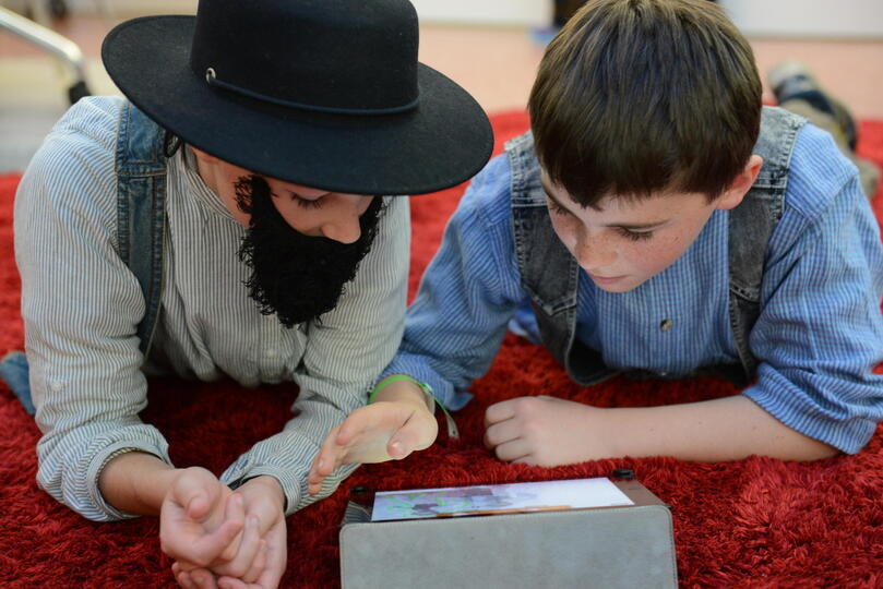Two boys dressed up in gold mining costumes looking at an iPad