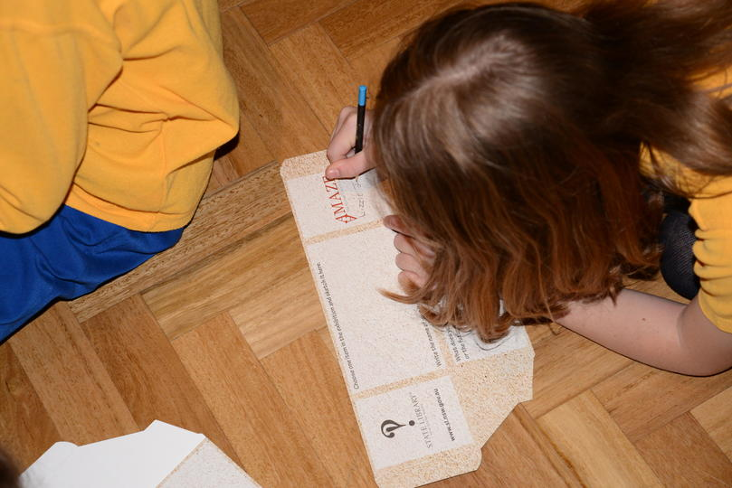 A child writing on an activity box