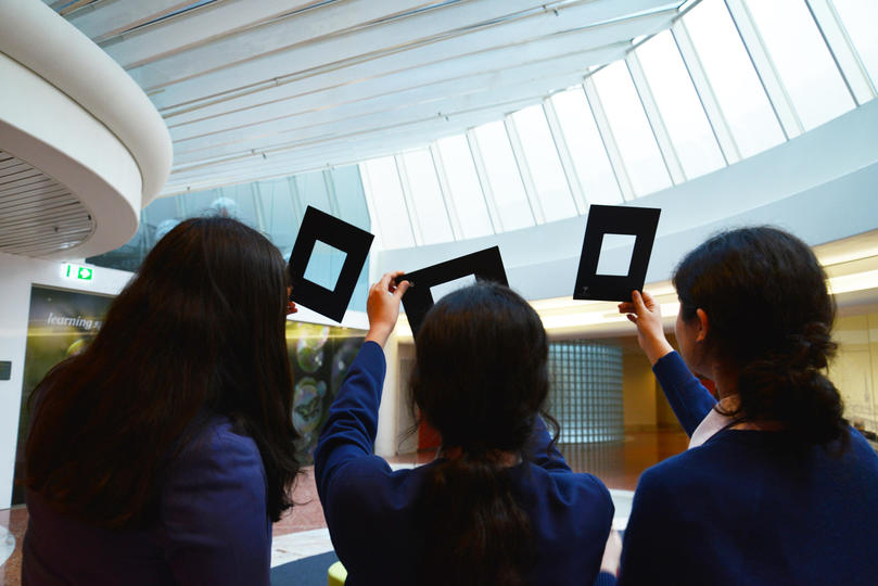 Three students holding up frames