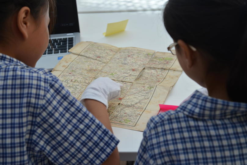 Two students looking at an old map