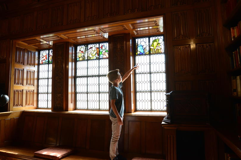 A child looking through the stained glass windows in the State Library Shakespeare Room