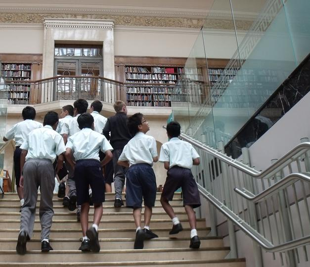 boys walking up the stairs in the library