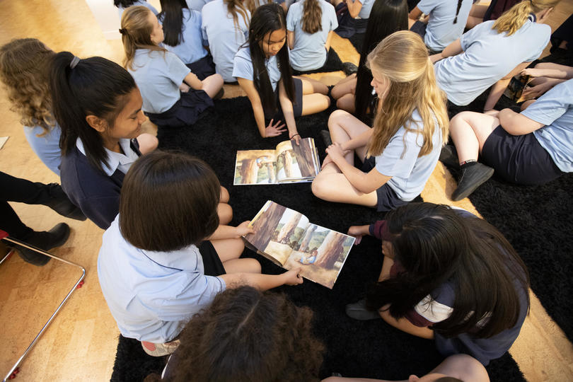 A group of students gathered around picture books
