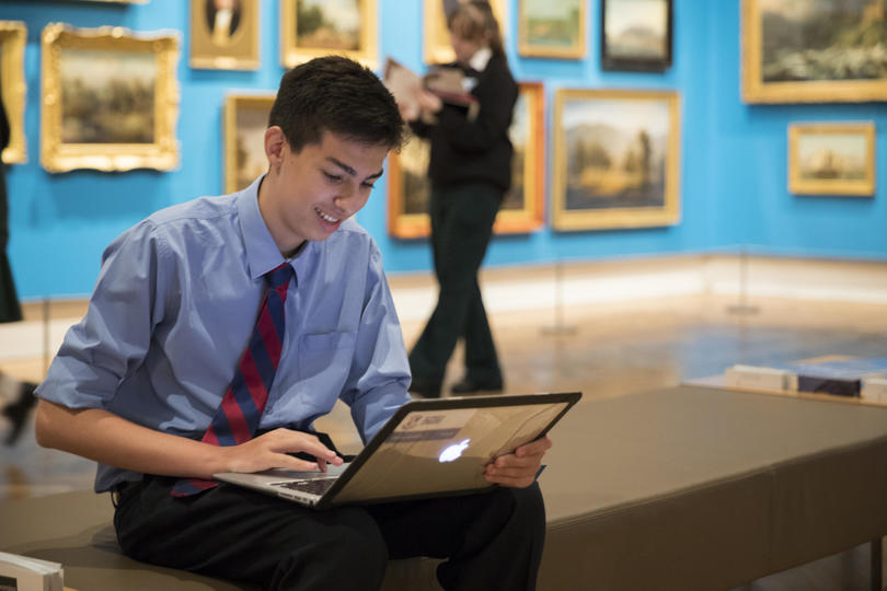 A student on his laptop in the Paintings from the Collection gallery