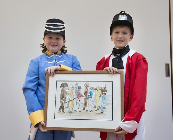 two boys in costume holding a framed image
