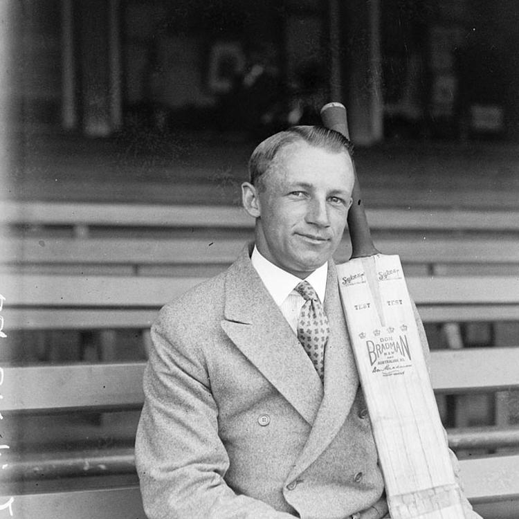 Man holding cricket bat sitting in stands