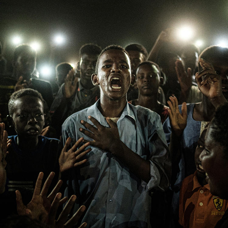 A young Sudanese man stand with his hand on his heart, mid sentence. He is surrounded by a crowd holding up their mobile phones to illuminate him.