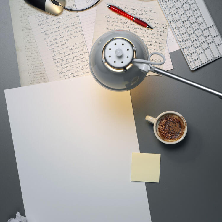 Coffee cup and pen and hand written paper under a lamp