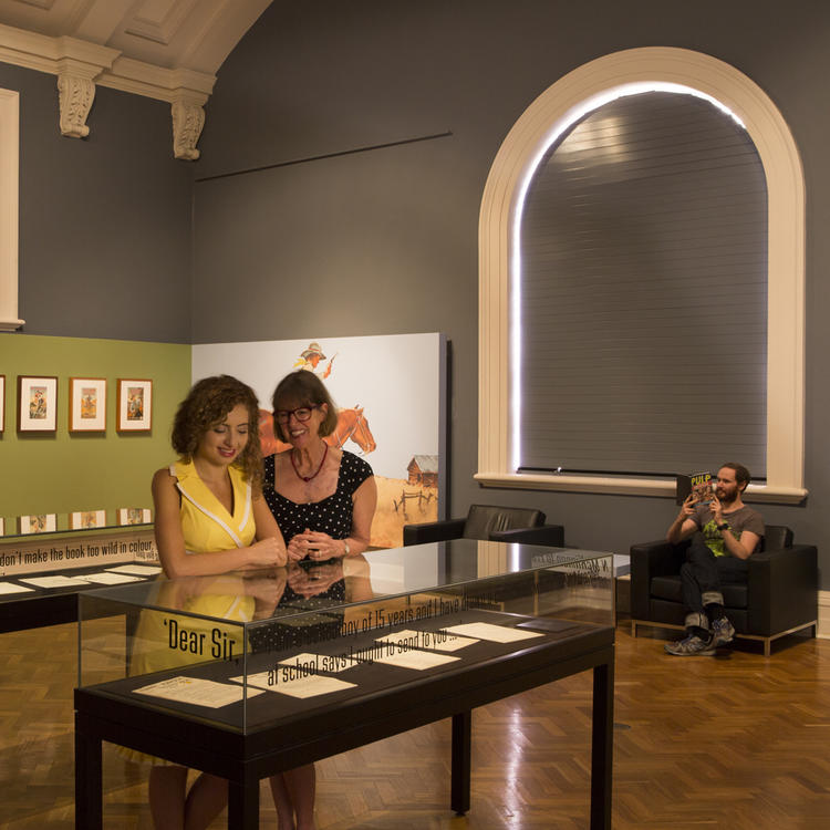 Two women in large gallery looking at glass case
