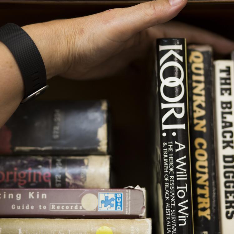 A hand organising books on a wooden shelf