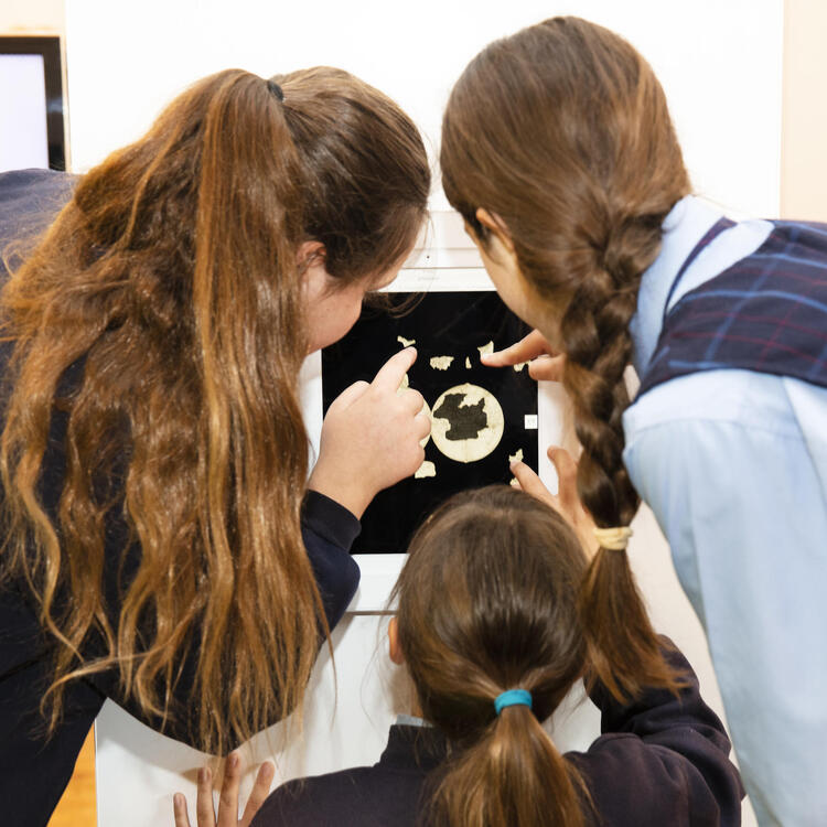Three students looking at an iPad