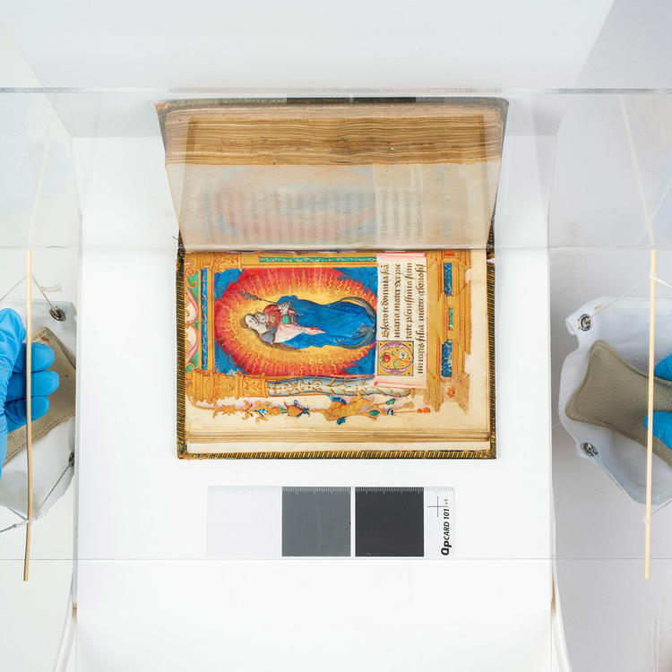 A top-down view of an illuminated book being imaged, with gloved hands in view.