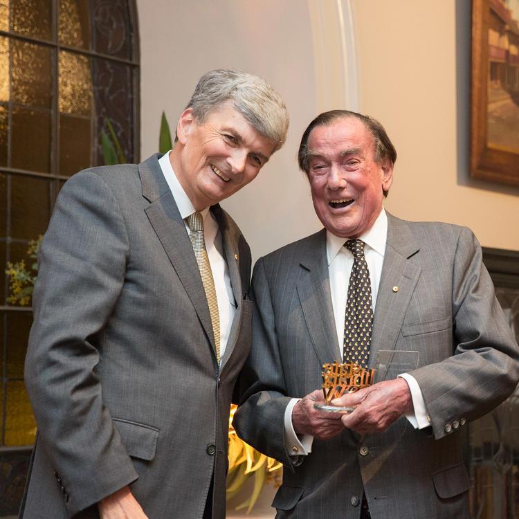 Two men holding award