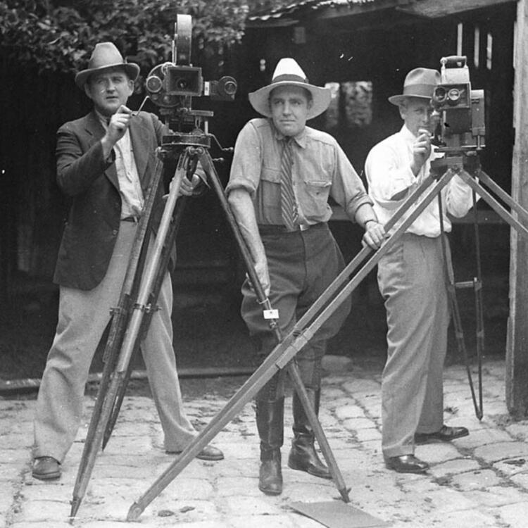 3 men standing behind cameras filming