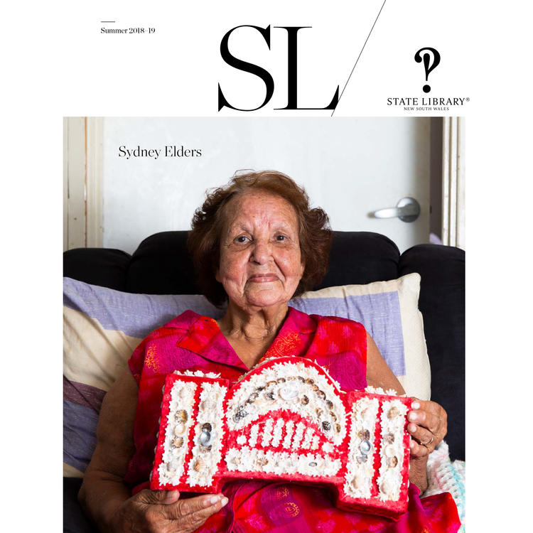 Magazine cover of an older woman proudly showing her crafted handiwork made of shells.