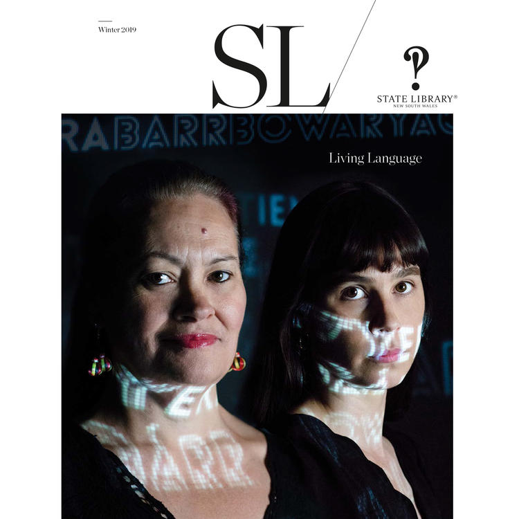 Magazine cover featuring two women with text projected in light.