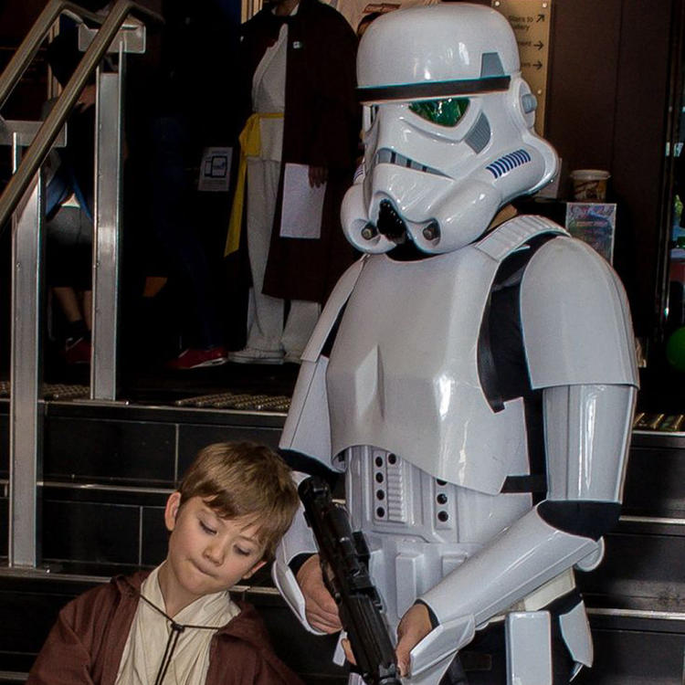 Boy standing next to man dressed as StormTrooper in white costume