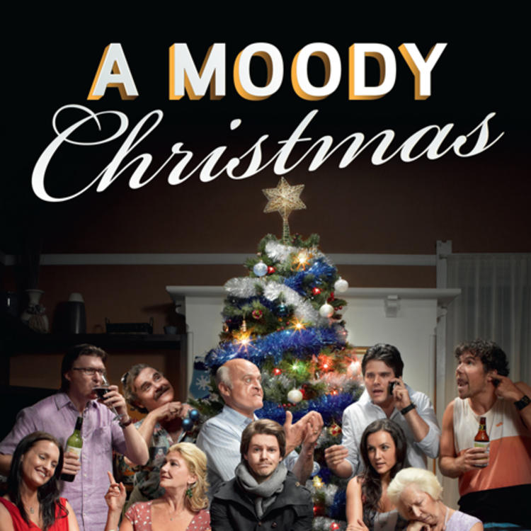 Group of people sitting around a Christmas Tree celebrating Christmas for A Moody Christmas