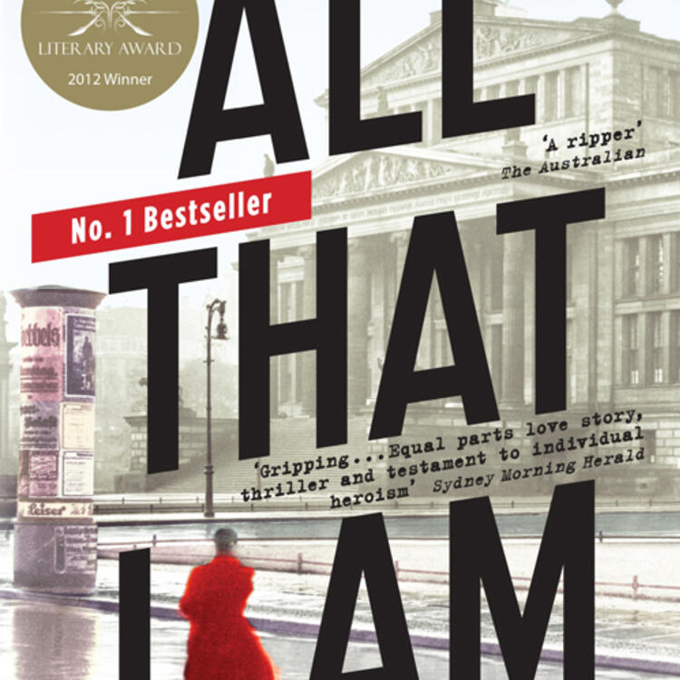 Woman in a street wearing a long coat facing a large historic old building for book cover of All That I am by Anna Funder
