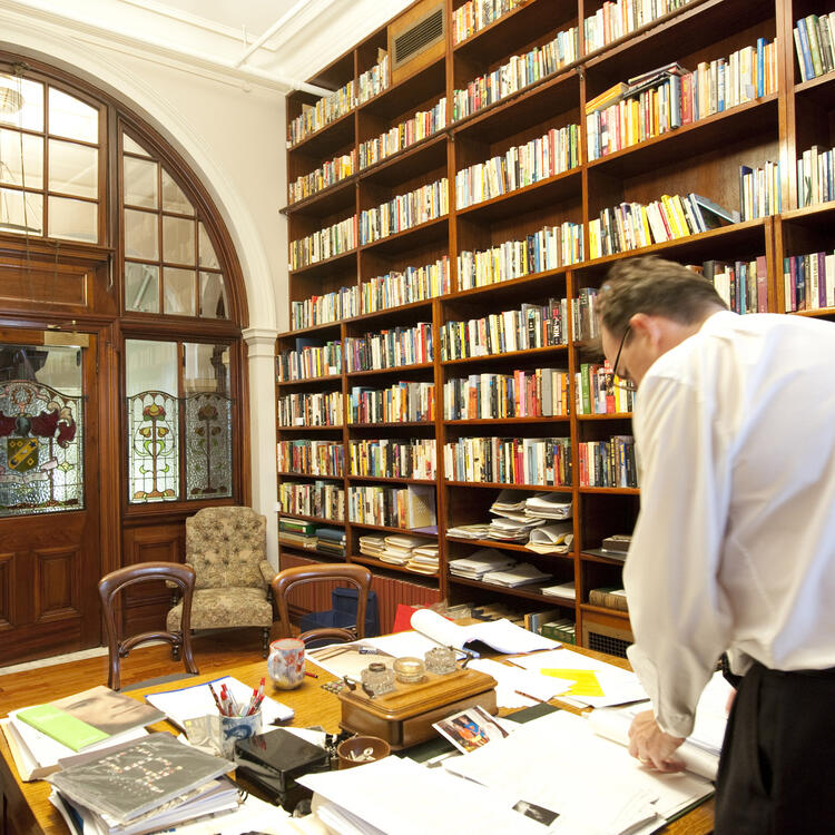 Man standing behind desk in room with many bookshelves and papers