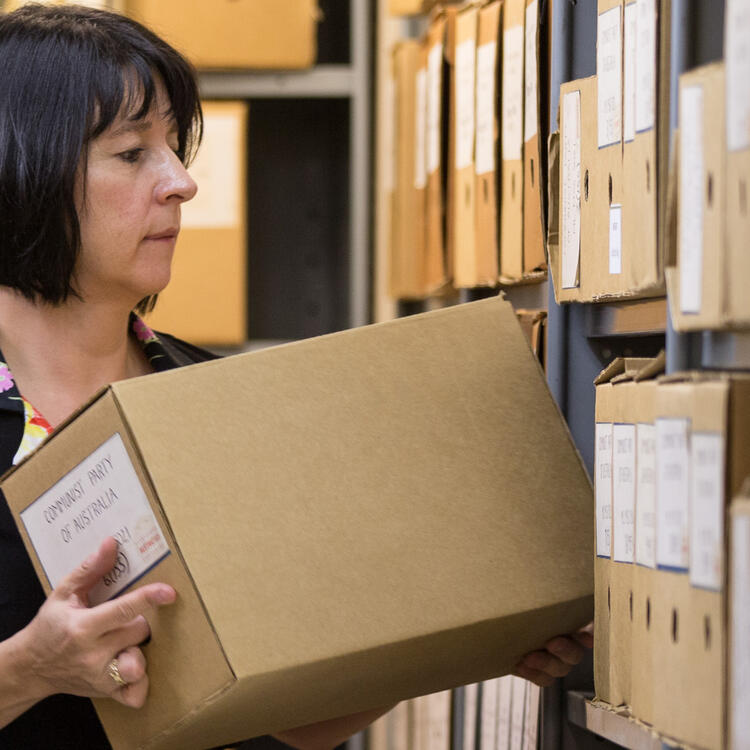 Woman filing away boxes on shelves