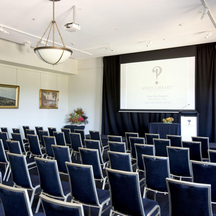 Room with chairs in rows facing a presentation stage with lecturn