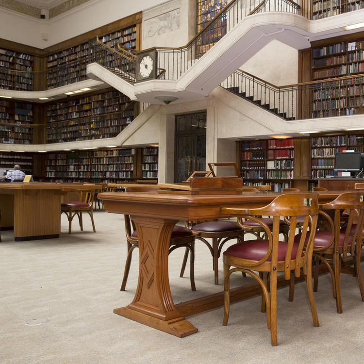 Tables and chairs in large book case lined room