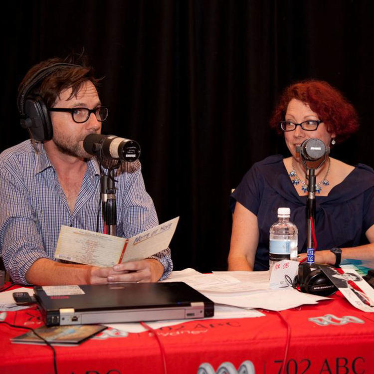 Man and woman sitting at table with microphones