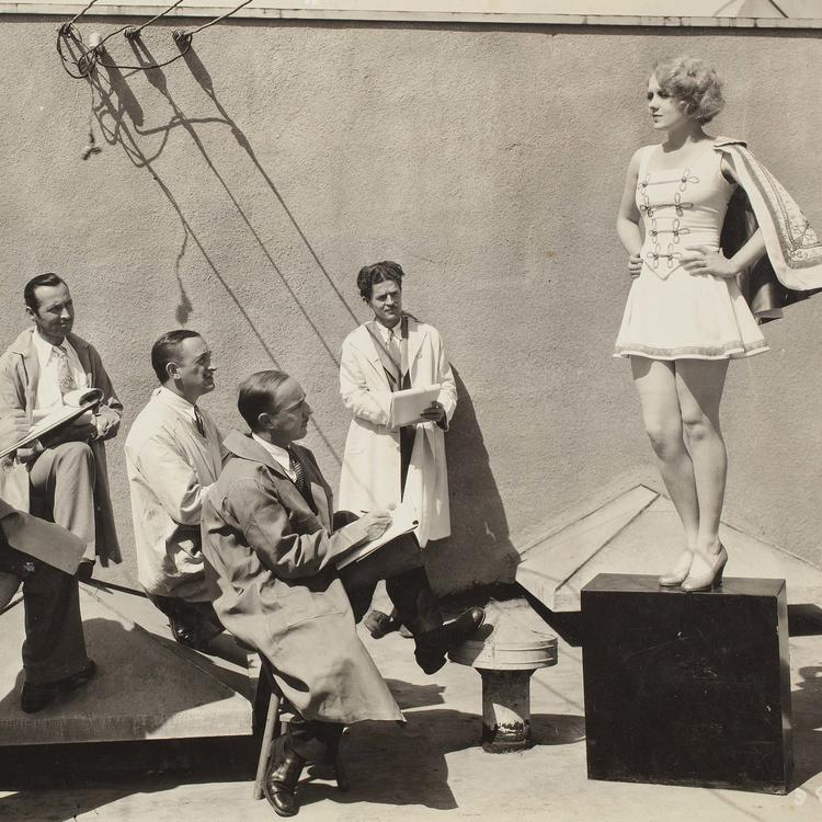 Several men in white coats sketching a young woman modelling