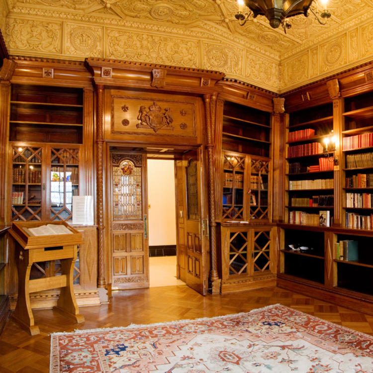 Wood panelled room with bookcase and ornate rug