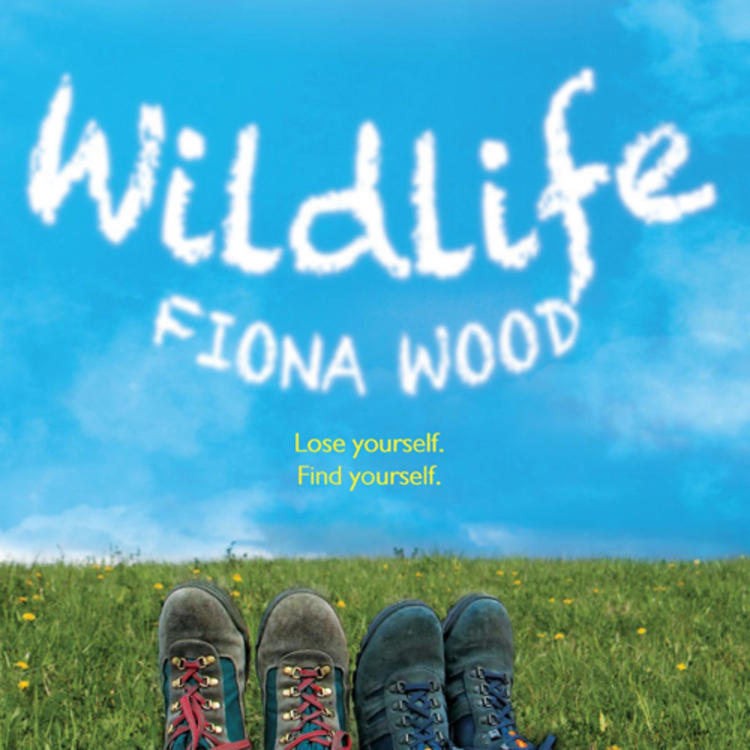 Two sets of legs with shoes lying on a grass on book cover of Wildlife by Fiona Wood