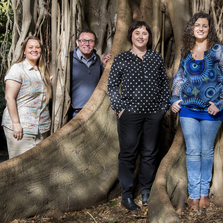 6 people standing in front of a tree
