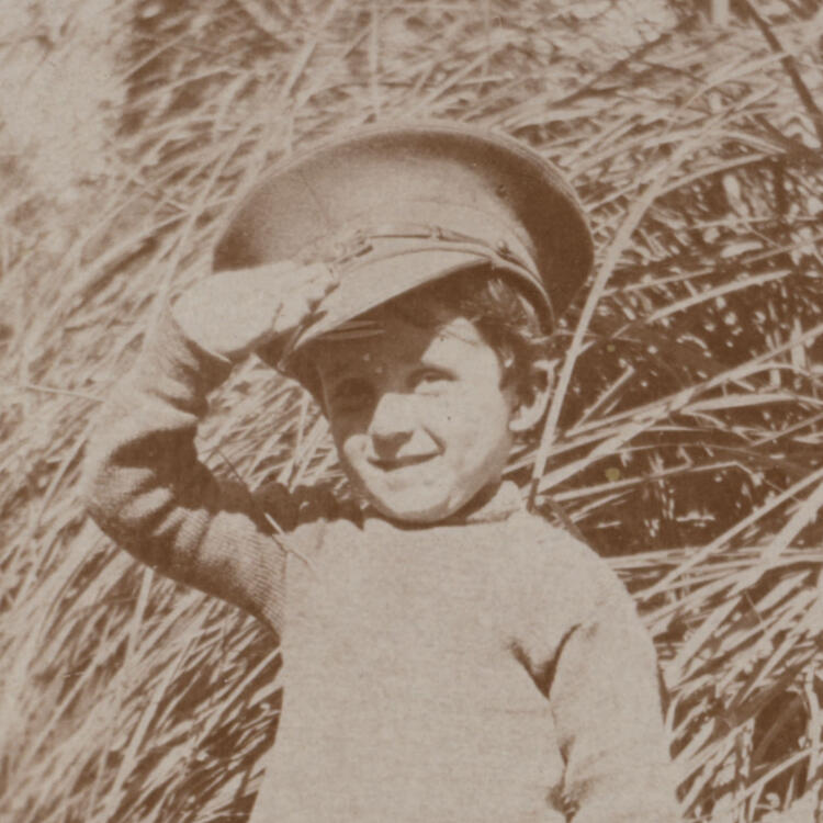 A sepia photograph of a boy wearing an oversized army cap, standing and saluting.